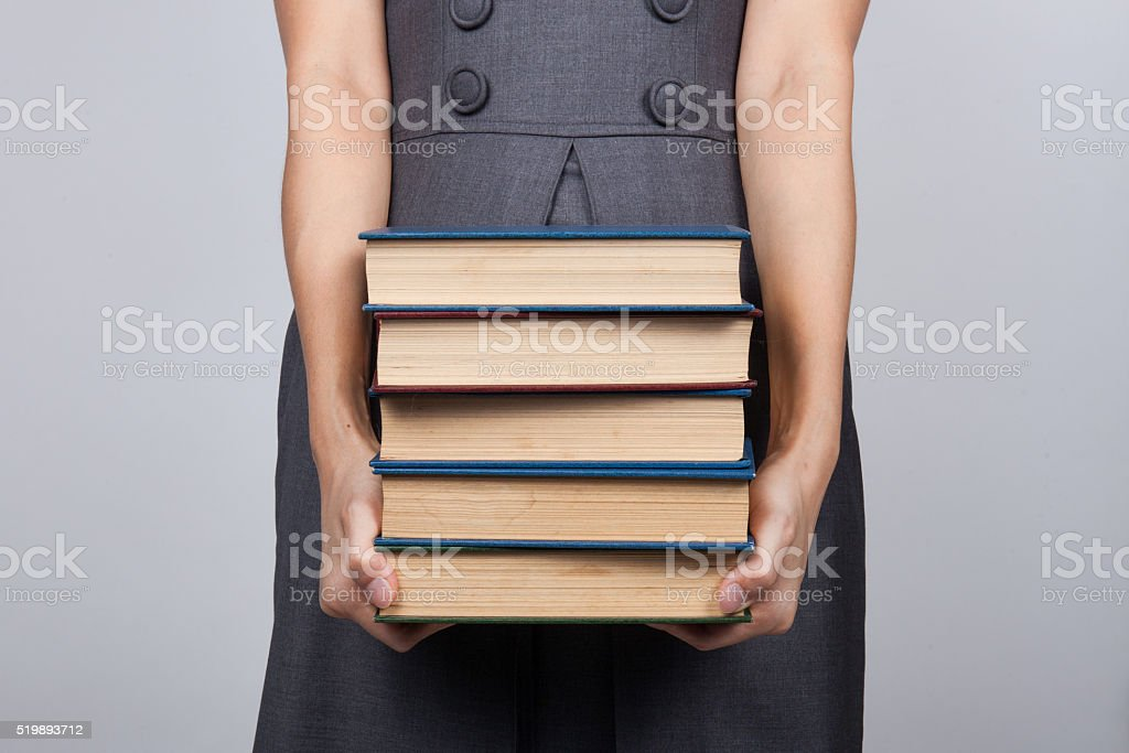 woman carrying a pile of books at office stock photo