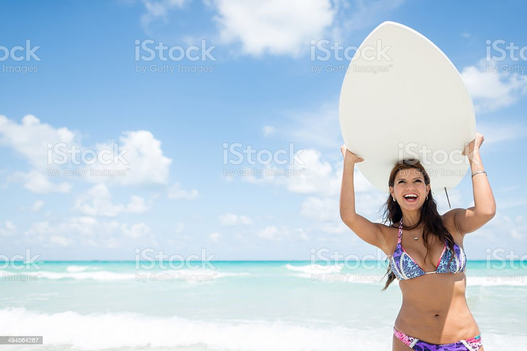 Woman carrying a surfboard royalty-free stock photo