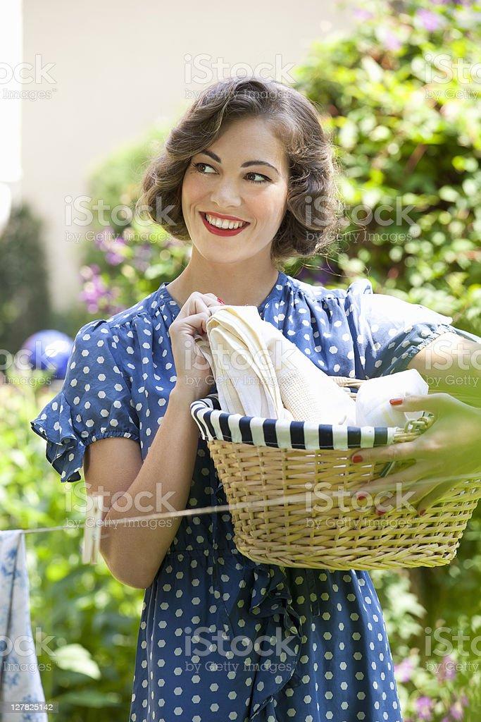 Woman carrying basket in backyard royalty-free stock photo