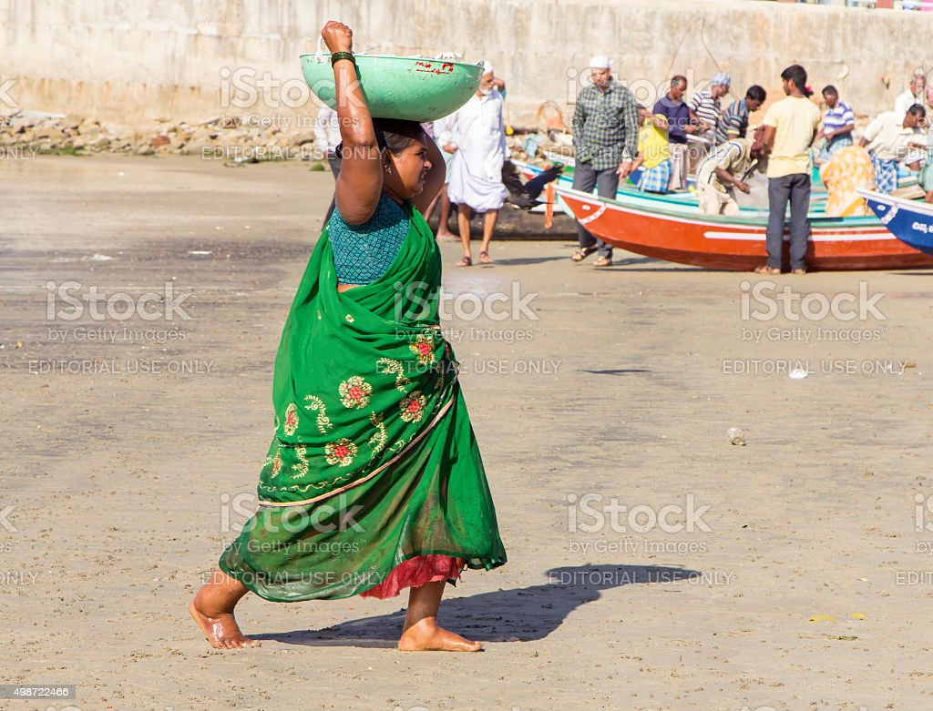 Woman carrying basket of fish, Murudeshwar, Karnataka, India stock photo