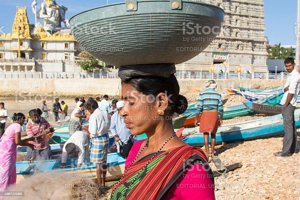 Woman carrying basket on head, Murudeshwar, Karnataka, India stock photo