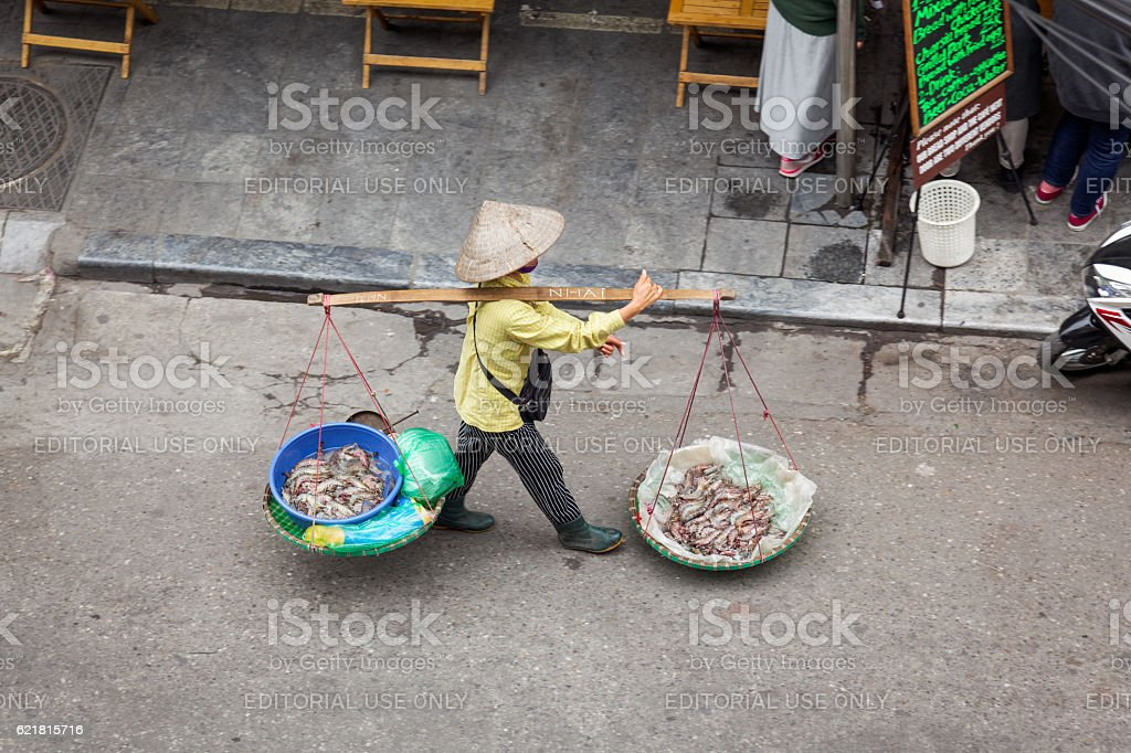 Woman carrying baskets with shrimps in Hanoi stock photo