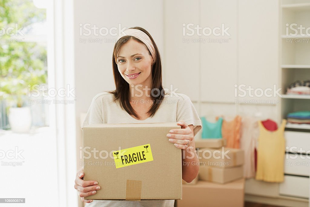 Woman carrying box with fragile sticker into new house royalty-free stock photo
