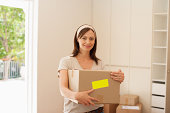Woman carrying box with fragile sticker into new house