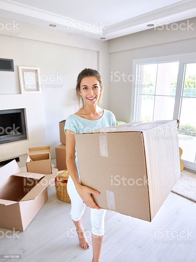 Woman carrying cardboard box for new home stock photo