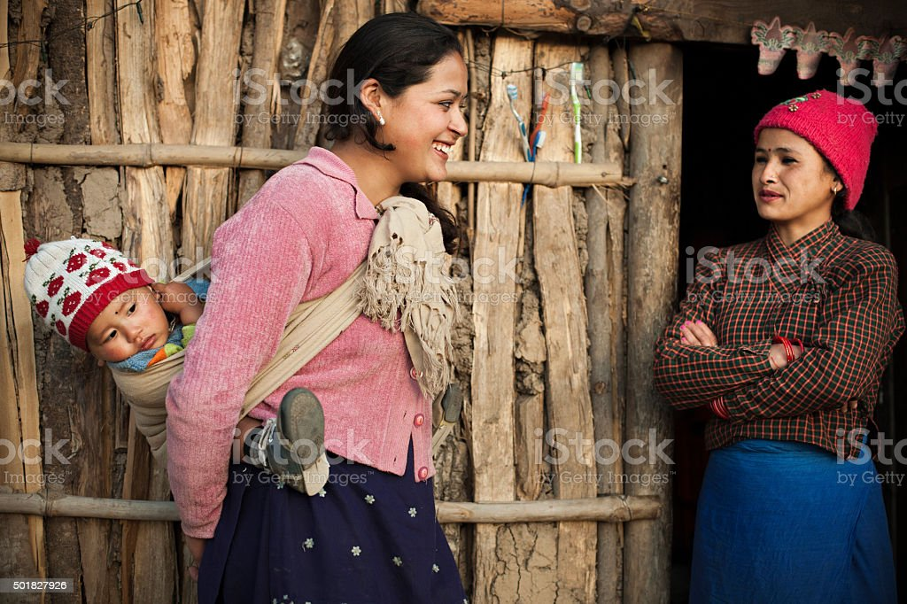 Woman carrying child on back and talking to other woman. stock photo