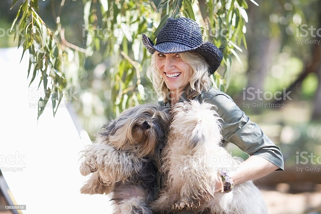 Woman carrying dogs outdoors stock photo