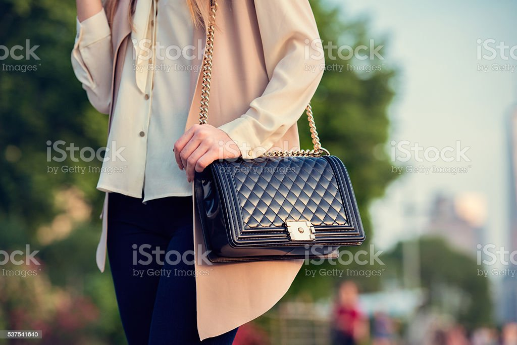 Woman carrying elegant purses bag at city park stock photo