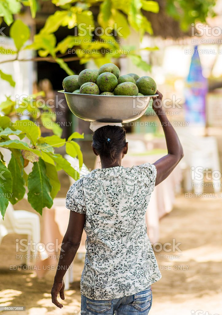 Woman carrying fruits stock photo
