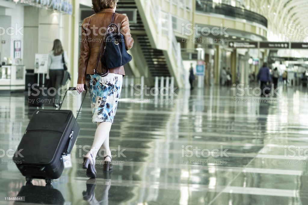 A woman carrying her suitcase in an airport stock photo