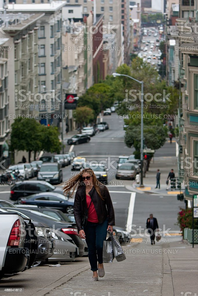 Woman Carrying Shopping Bags Climbs Steep Steps In Nob Hill stock photo