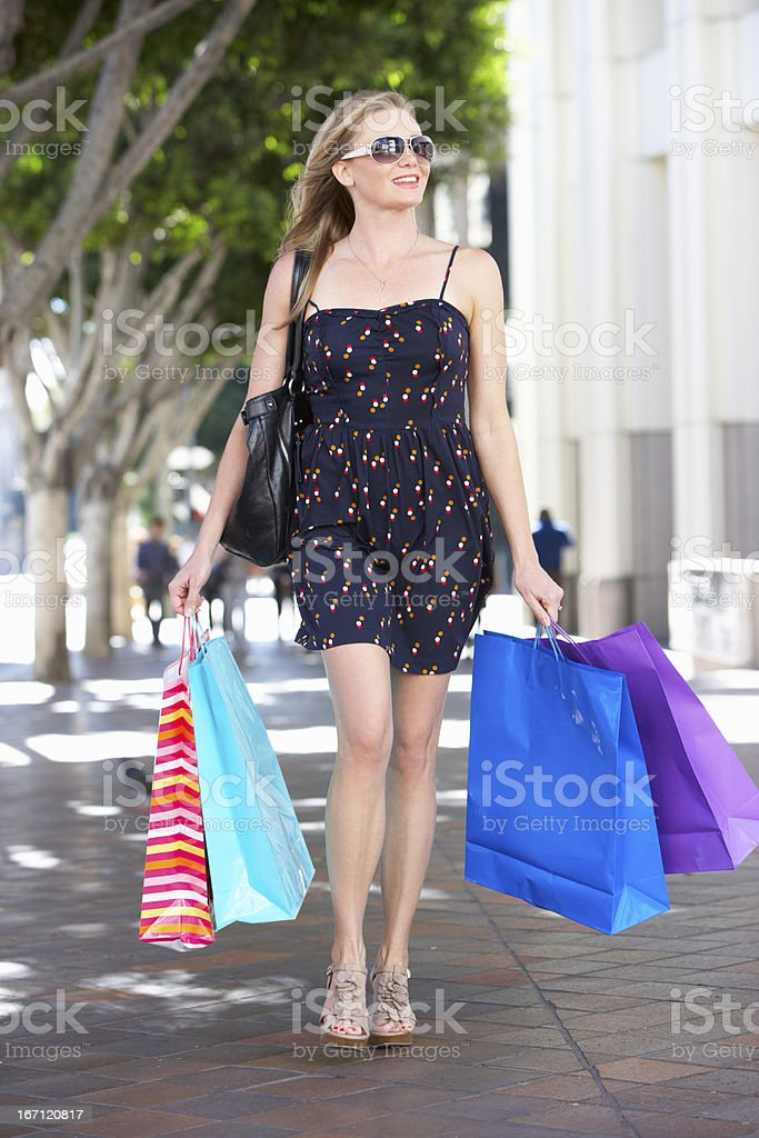 Woman Carrying Shopping Bags On City Street royalty-free stock photo
