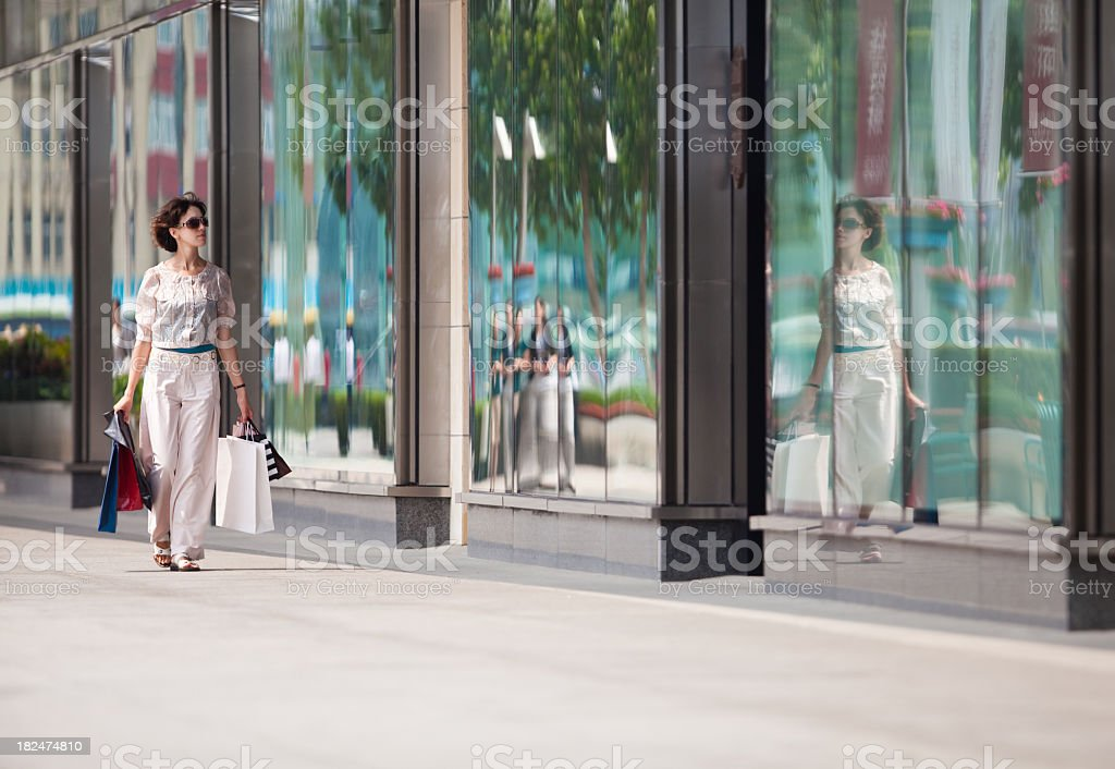 Woman carrying shopping bags walking down a sidewalk royalty-free stock photo