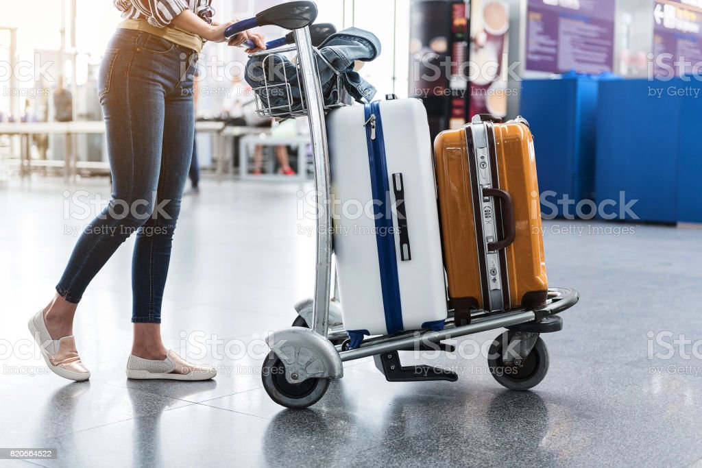 Woman carrying suitcases across hall of airport stock photo