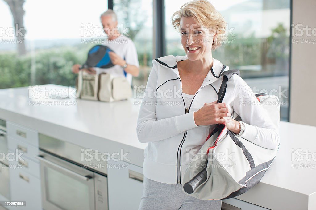 Woman carrying tennis racquet in gym bag stock photo