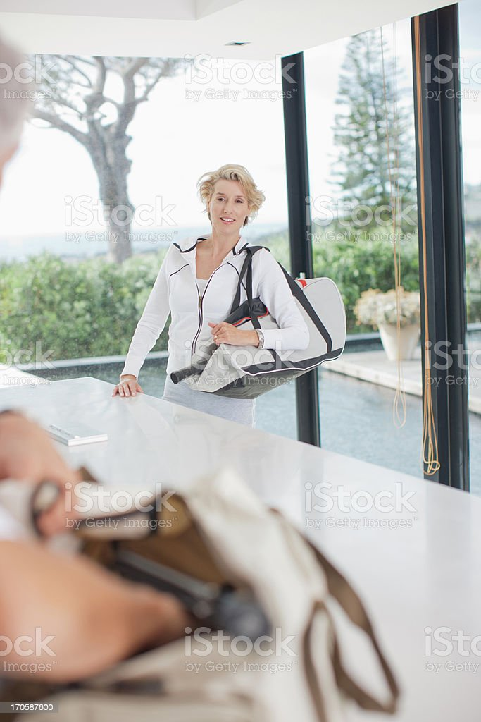Woman carrying tennis racquet in gym bag royalty-free stock photo
