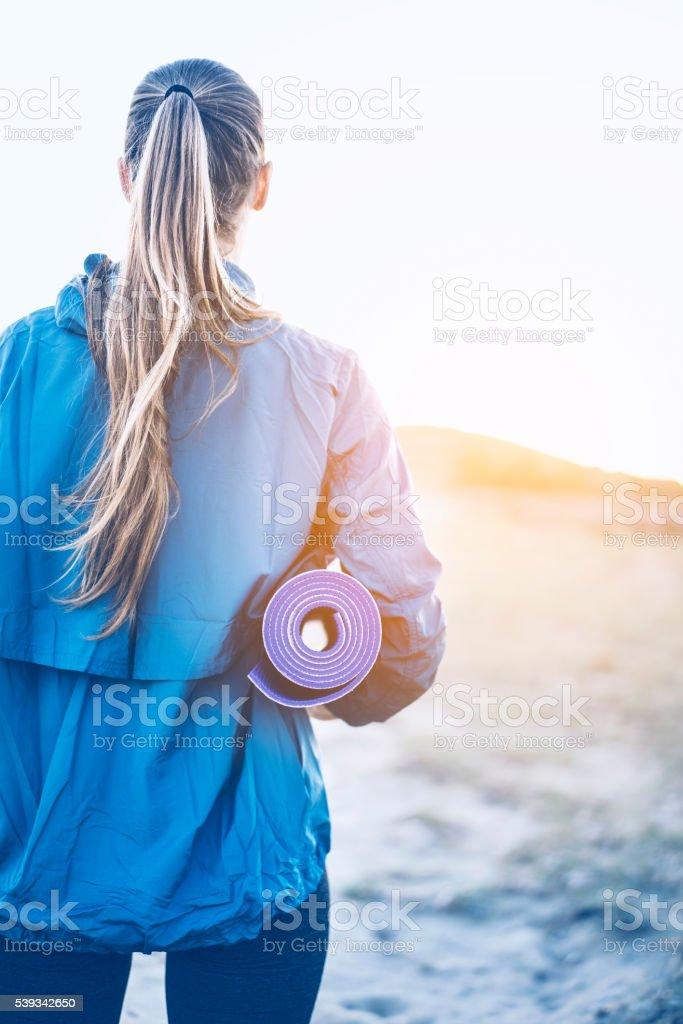 Woman carrying yoga mat stock photo