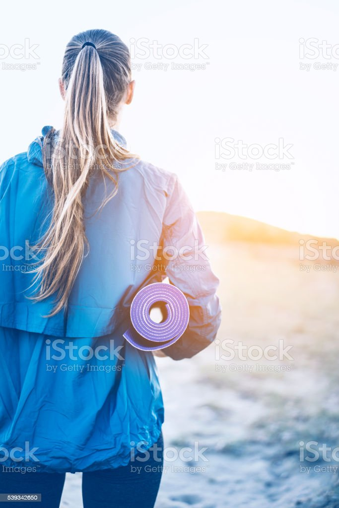 Woman carrying yoga mat stock photo