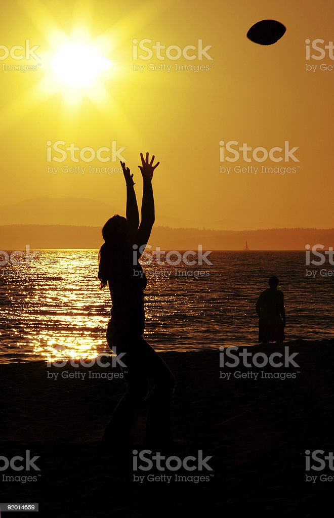 Woman Catching Football at Beach royalty-free stock photo