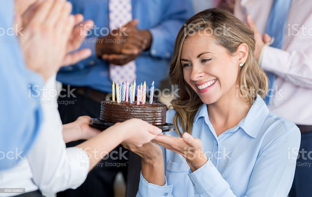 Woman celebrating her birthday at the office stock photo