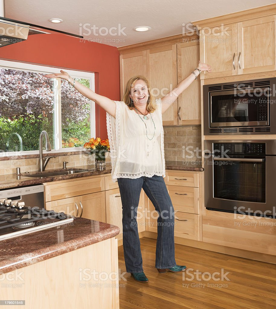 Woman Celebrating Her Remodeled Kitchen stock photo