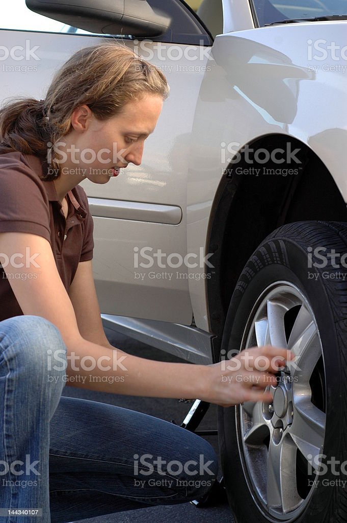 Woman Changing a Tire royalty-free stock photo