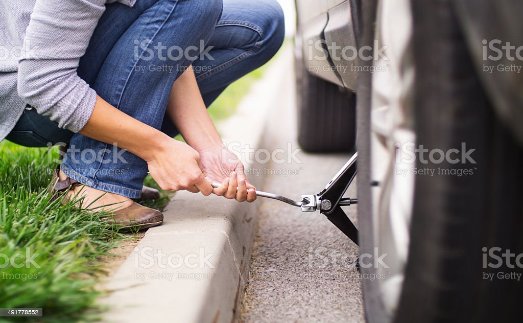 Woman changing flat tire on her car. stock photo