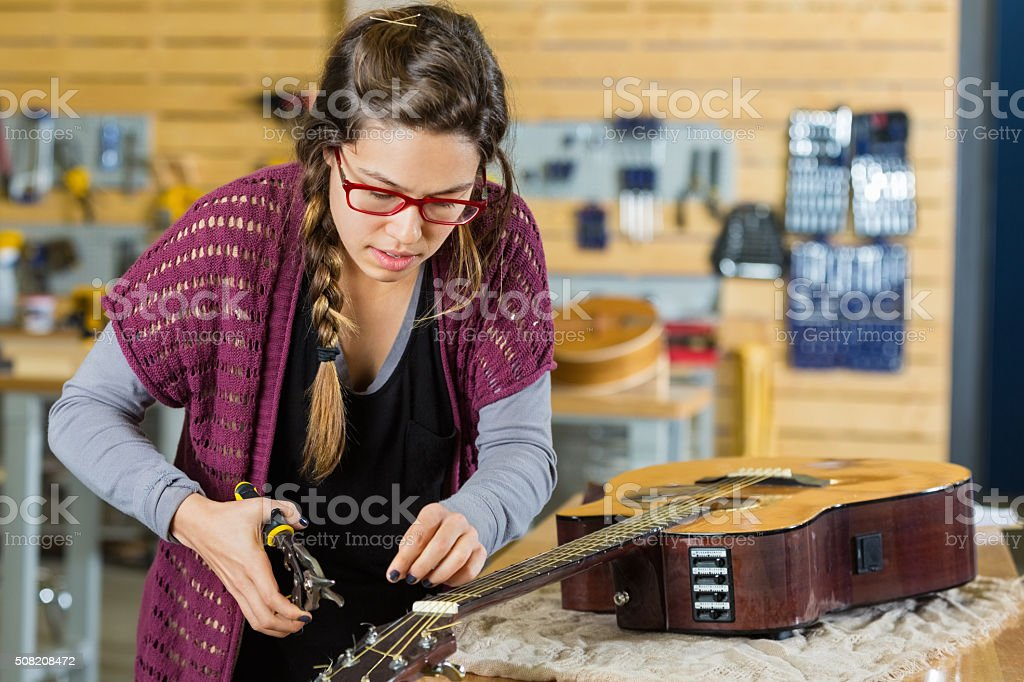 Woman changing guitar strings while working in instrument repair shop stock photo