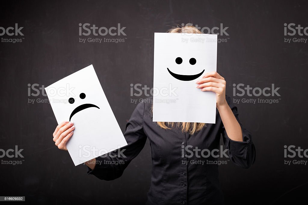 Woman changing smileys on her face stock photo