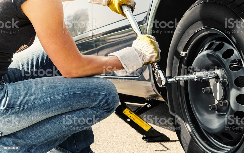Woman changing tire car stock photo