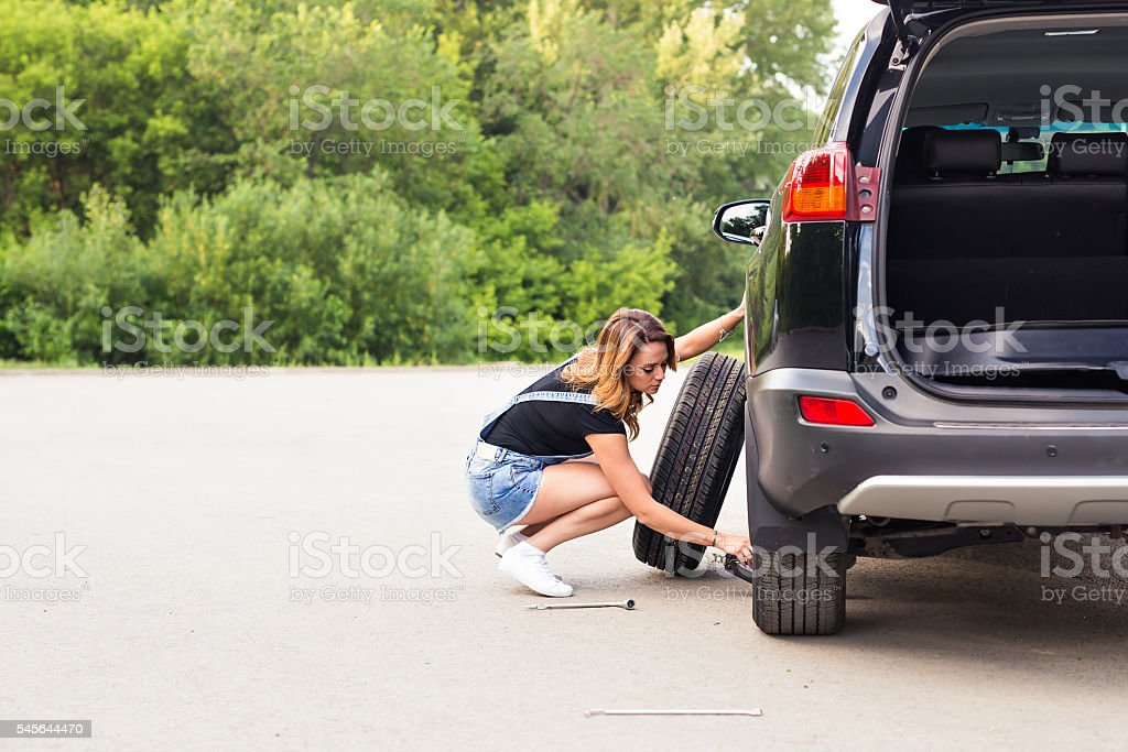 Woman changing tire on a road stock photo