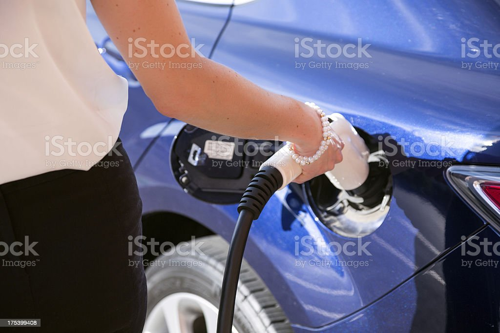 Woman Charging an Electric Vehicle at Charging Station stock photo