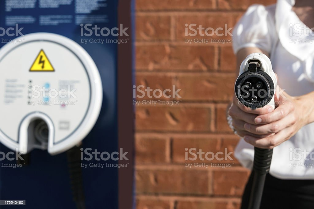 Woman Charging an Electric Vehicle at Charging Station royalty-free stock photo