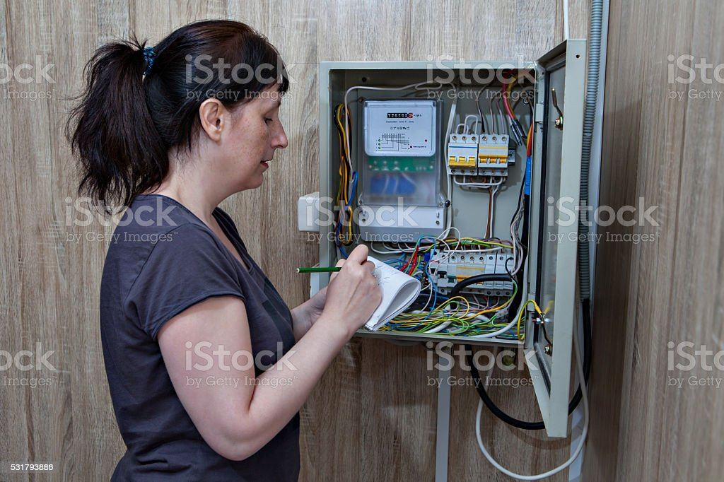 Woman checking electric counter, standing near electricity switchgear indoors. stock photo