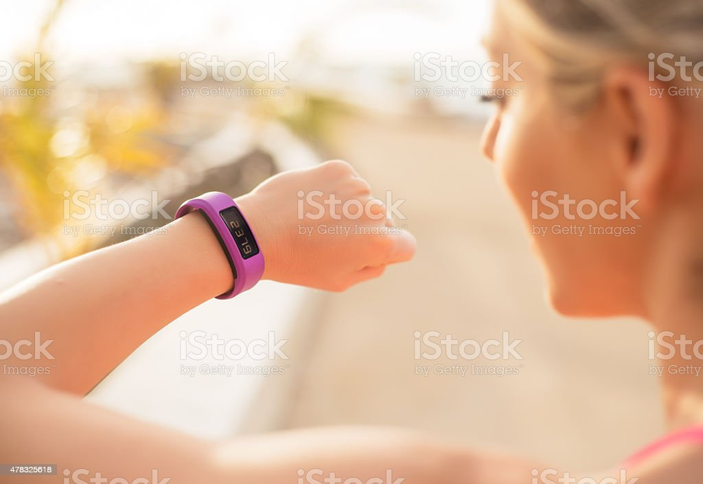Woman checking fitness wearable device stock photo