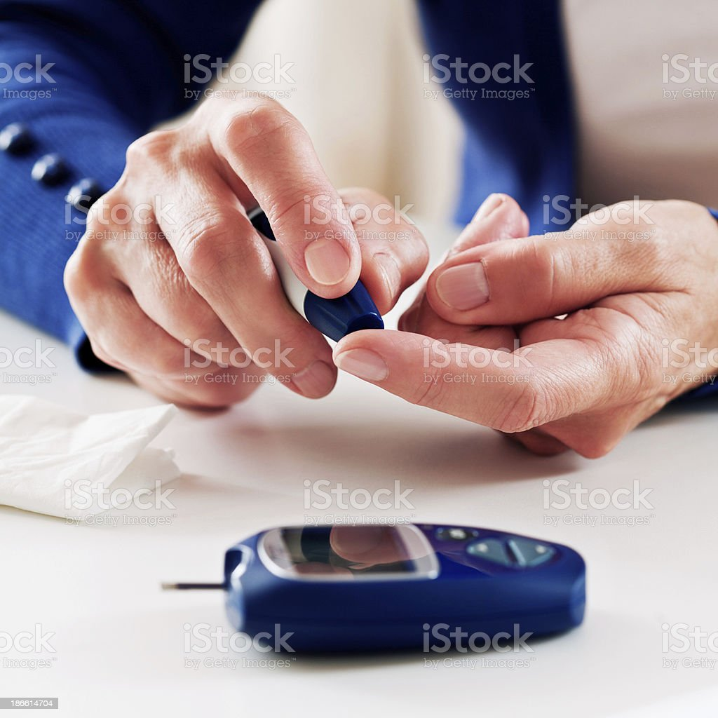 Woman checking glucose level stock photo
