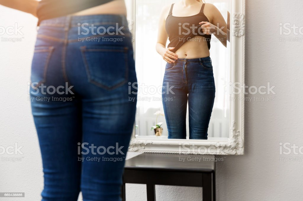 woman checking her body in front of mirror stock photo