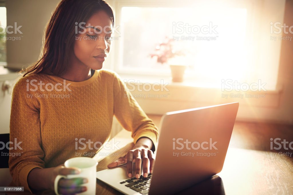 Woman checking her computer and holding coffee cup stock photo
