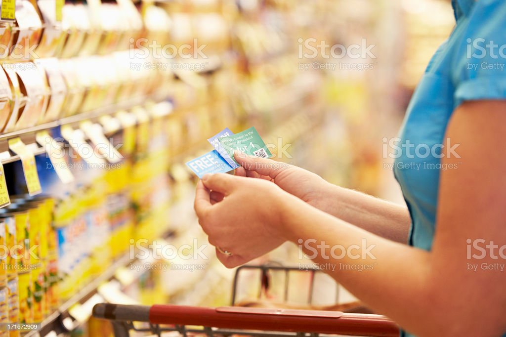 A woman checking her coupons in the store stock photo