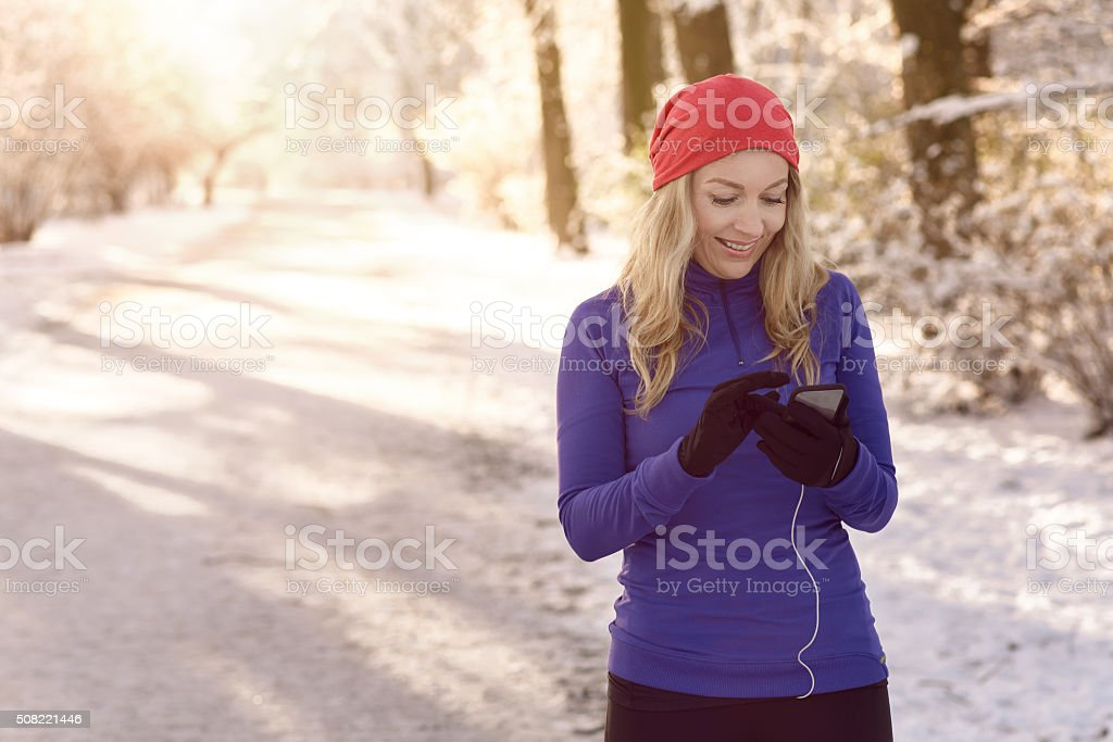 Woman checking her mobile on a winter walk stock photo