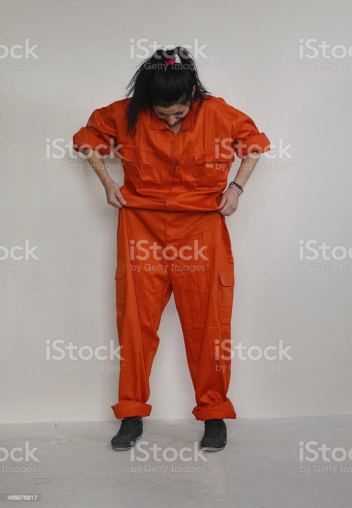 Woman checking her orange overalls stock photo