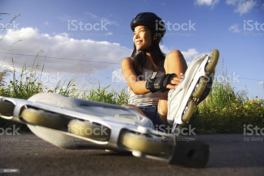A woman checking her rollerblades on a sunny day stock photo