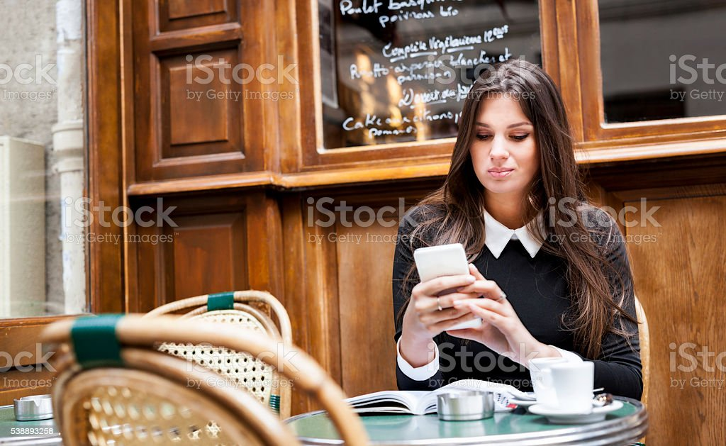 Woman Checking Her Social Media While Relaxing In A Cafeteria stock photo