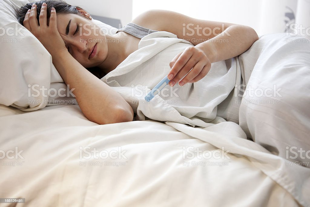 Woman Checking Her Temperature in Bed stock photo