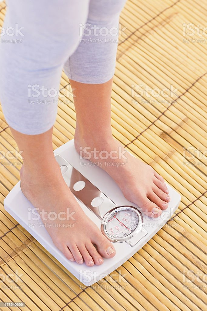 Woman checking her weight on weighing machine stock photo