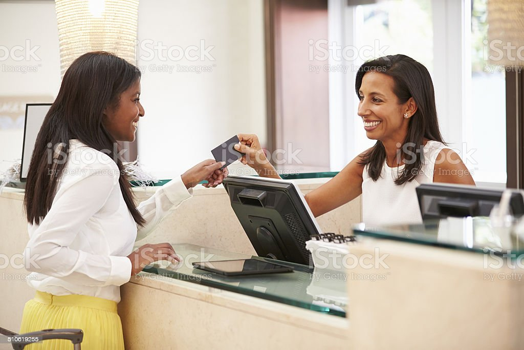 Woman Checking In At Hotel Reception stock photo
