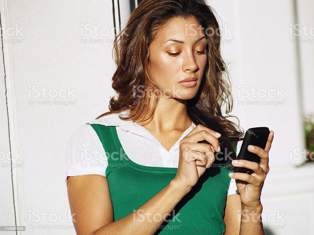 Femme vérifiant les messages sur son téléphone photo libre de droits