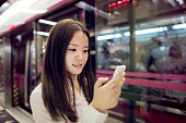 Woman checking mobile phone in subway