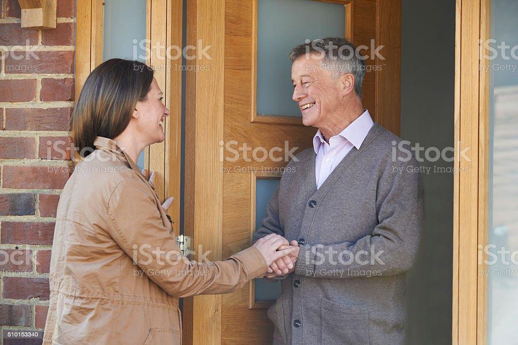 Woman Checking On Elderly Male Neighbor stock photo