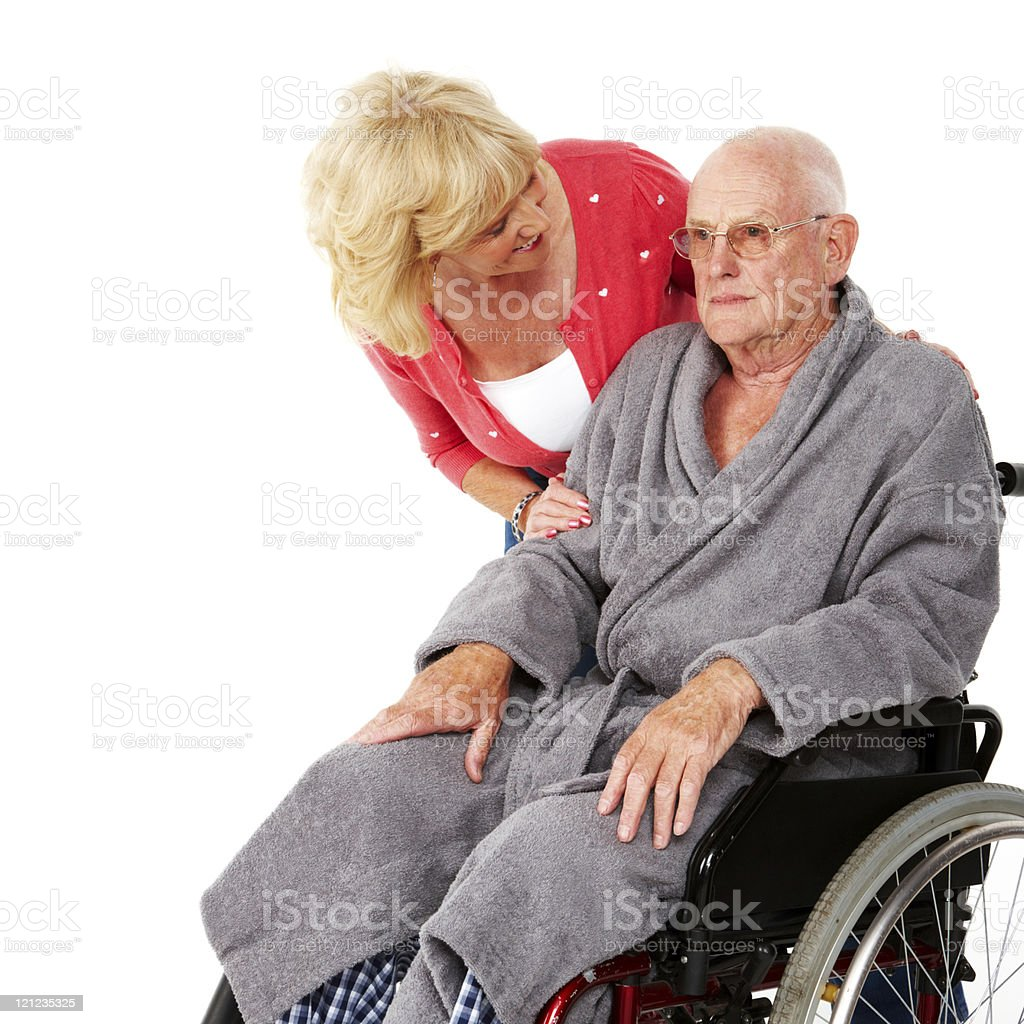 Woman Checking on Elderly Man in a Wheelchair - Isolated royalty-free stock photo